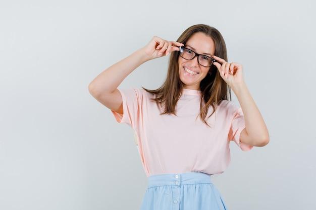 Tシャツ、スカート、陽気に見える眼鏡に指を保持している若い女性。正面図。