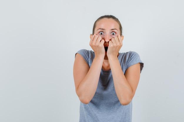 Молодая женщина держит кулаки на лице в серой футболке и выглядит испуганной. передний план.