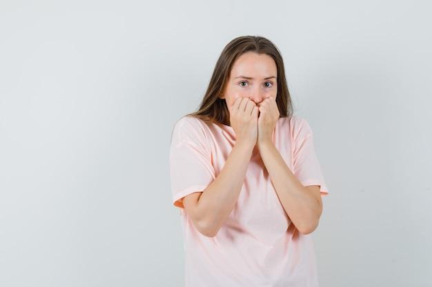 ピンクのtシャツを着て拳を口に抱えて怖がっている若い女性。正面図。