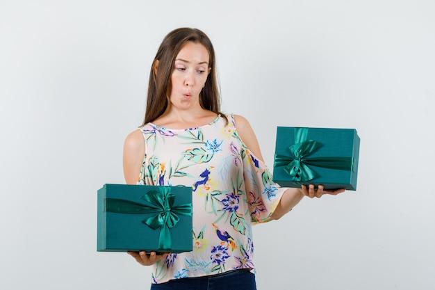 Молодая женщина держит подарочные коробки в рубашке, джинсах и выглядит изумленно, вид спереди.