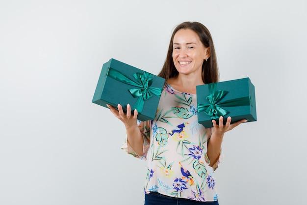 Giovani contenitori di regalo femminili della holding in camicia, jeans e vista allegra, vista frontale.