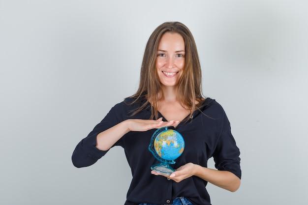Молодая женщина держит глобус в черной рубашке, джинсовых шортах и выглядит весело