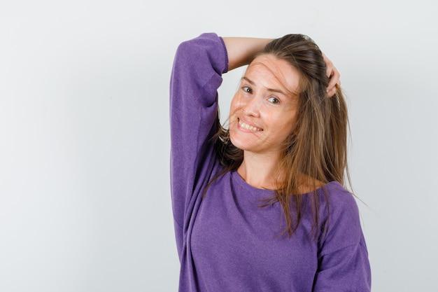 Giovane donna che tiene i capelli in mano in camicia viola e che sembra piacevole. vista frontale.