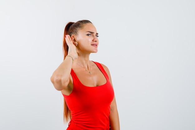 Молодая женщина держит руку за ухом в красной майке, штанах и смотрит любопытно, вид спереди.