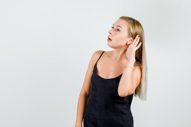 黒の一重項で聞くために耳の後ろで手をつないでいる若い女性