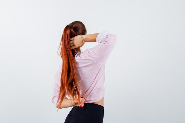 Молодая женщина держит руку за голову в повседневной рубашке и выглядит уверенно, вид сзади.