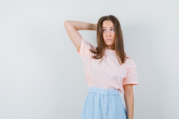 Tシャツ、スカート、躊躇して頭の後ろで手をつないでいる若い女性。正面図。