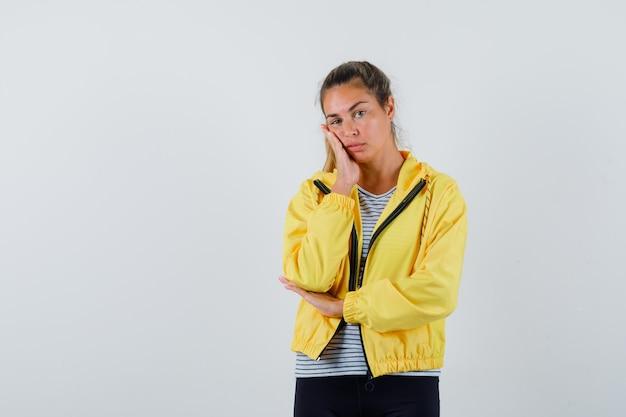 Giovane donna che tiene la mano sulla guancia in giacca, t-shirt e sembra carina, vista frontale.