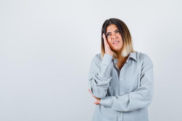 Giovane donna che tiene la mano sulla guancia in camicia oversize e sembra carina, vista frontale.