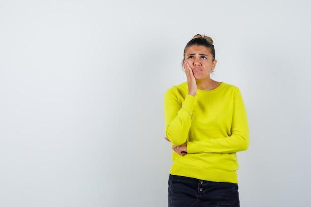 Giovane donna che tiene la mano sulla guancia in maglione, gonna di jeans e sembra pensierosa