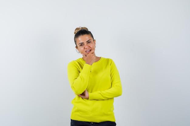 Giovane donna che tiene la mano sul mento in maglione, gonna di jeans e sembra attraente