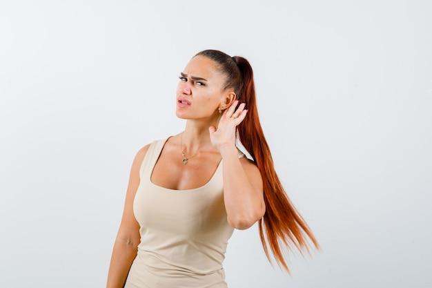 Giovane donna che tiene la mano dietro l'orecchio in canottiera beige e guardando concentrato. vista frontale.
