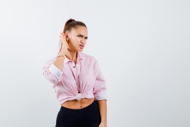 Giovane donna che tiene la mano dietro l'orecchio in camicia casual e guardando meravigliato, vista frontale.