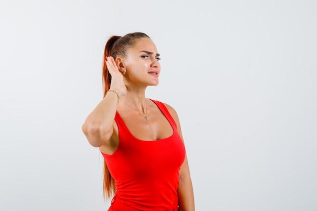 Giovane donna che tiene la mano dietro l'orecchio in canottiera rossa, pantaloni e guardando curioso, vista frontale.