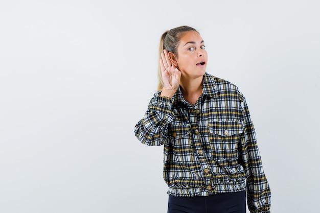 Giovane donna che tiene la mano dietro l'orecchio in maglietta, pantaloncini e guardando curioso, vista frontale.