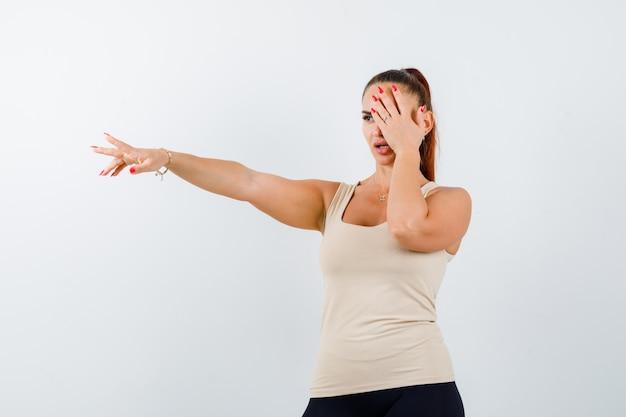 Giovane donna che tiene la mano sull'occhio mentre allunga il braccio in canottiera beige e sembra seria, vista frontale.