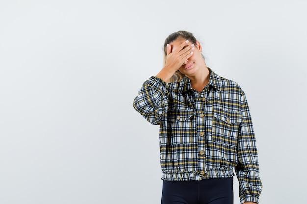 Giovane donna che tiene la mano sugli occhi in maglietta, pantaloncini e sembra carino. vista frontale.