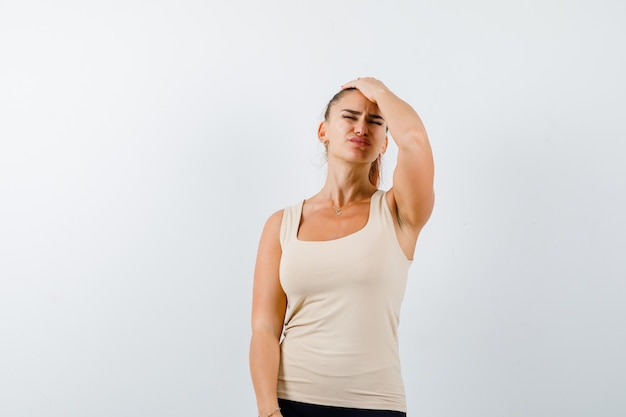 Young female holding hand on head in beige tank top and looking exhausted