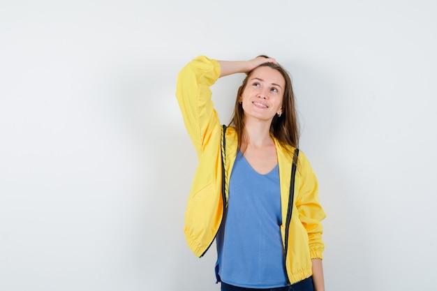 Giovane donna che tiene la mano sulla testa in t-shirt, giacca e sembra sognante, vista frontale.