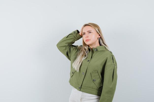 Giovane donna che tiene la mano sulla testa mentre pensa in giacca verde, jeans e sembra esitante. vista frontale.