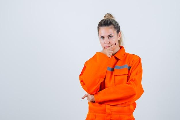 Giovane donna che tiene la mano sulla sua mascella in uniforme da lavoro e guardando pensieroso. vista frontale.