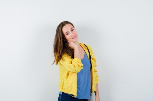 Giovane donna che tiene la mano sul collo in maglietta, giacca e sembra attraente, vista frontale.