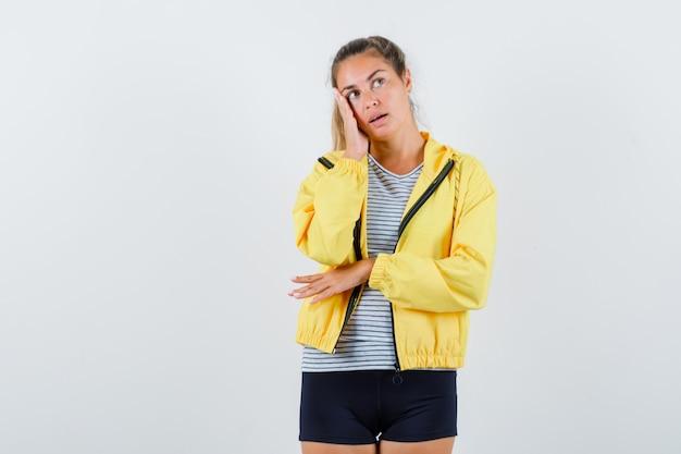 ジャケット、tシャツで頬に手をつないで、夢のような、正面図を探している若い女性。
