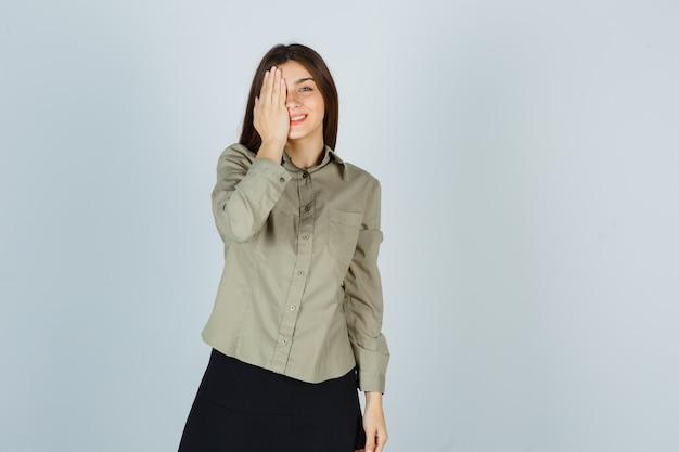 シャツ、スカートで目をつないで陽気に見える若い女性