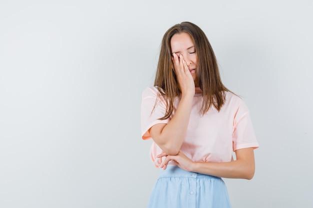 Tシャツ、スカートで顔に手をつないで、忘れっぽい若い女性。正面図。