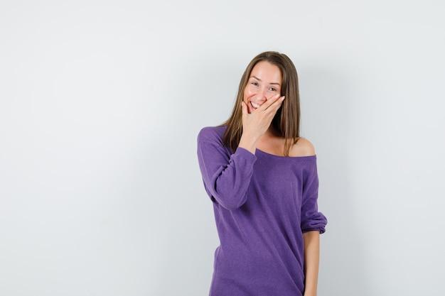 Молодая женщина держит руку на лице в фиолетовой рубашке и выглядит счастливой. передний план.