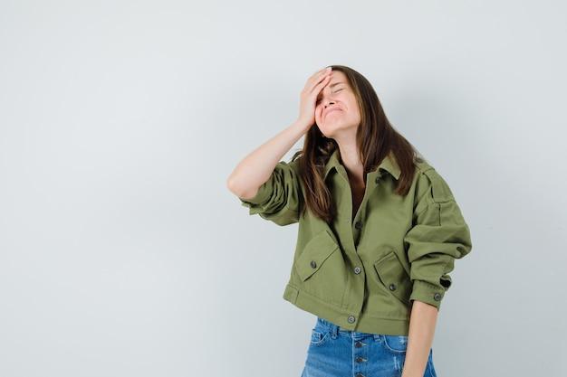 ジャケット、ショートパンツで額に手をつないで、物忘れ、正面図を探している若い女性。