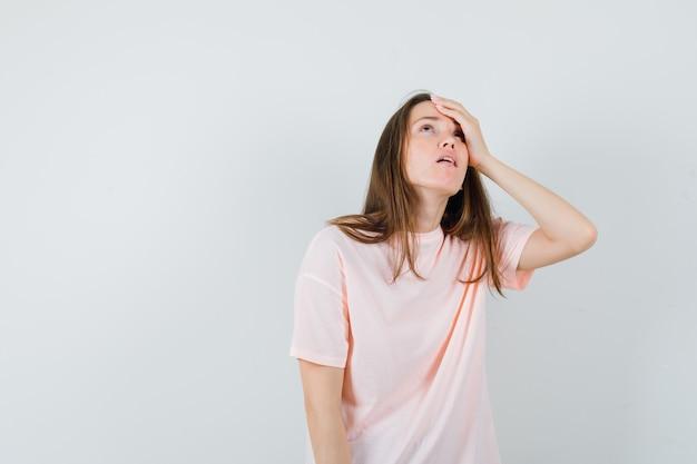 ピンクのtシャツで額に手をつないで、物欲しそうに見える若い女性。正面図。