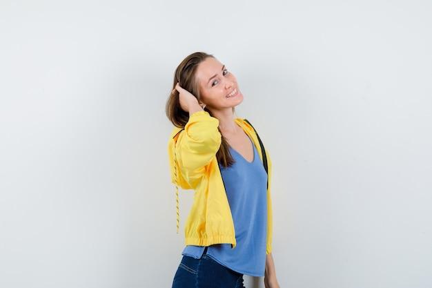 Молодая женщина держит руку на голове в футболке, куртке и выглядит очаровательно. передний план.