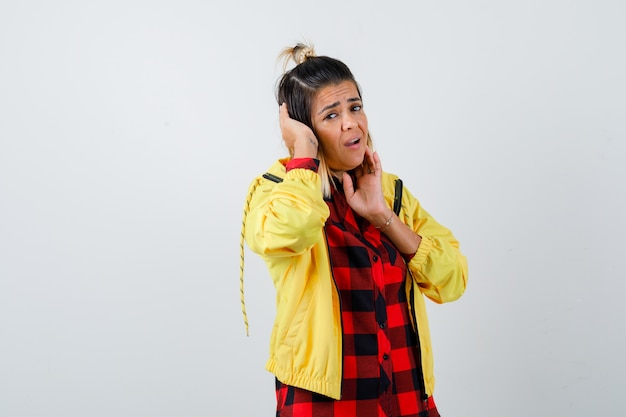 市松模様のシャツ、ジャケットの指で頬に触れ、問題を抱えているように見える間、頭に手を保持している若い女性。正面図。