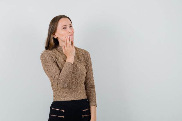 Молодая женщина держит руку на подбородке в блузке, юбке и выглядит болезненно, вид спереди. место для текста