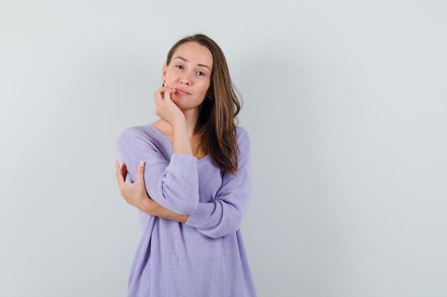 ライラックのブラウスでひじを抱きしめながら、あごに手をつないで印象的な若い女性 無料写真