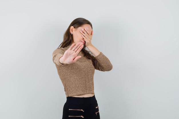 Молодая женщина, держащая руку на глазах, показывая жест остановки в блузке, юбке и выглядя испуганной, вид спереди.