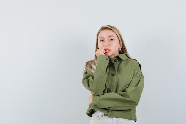 녹색 재킷, 청바지에 그녀의 턱에 손을 잡고 사려 깊은 찾고 젊은 여성. 전면보기.