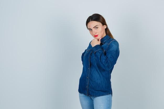 デニムシャツとジーンズで顎に手をつないで、魅力的に見える間、腰に手をつないでいる若い女性