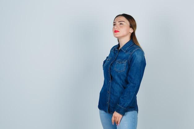 デニムシャツとジーンズで目をそらし、思慮深く見ながら腰に手をつないで若い女性