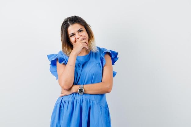 Молодая женщина держит руку на рту в синем платье и выглядит счастливой
