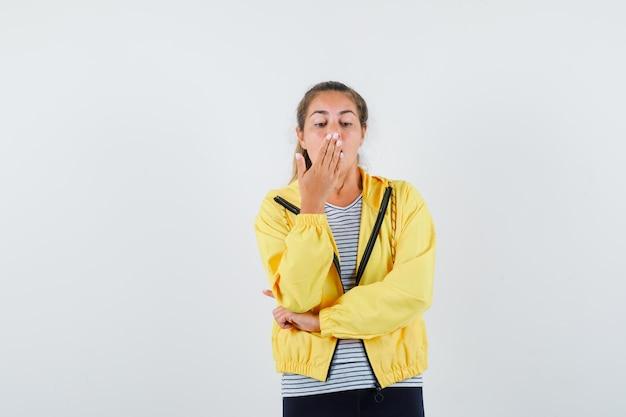 ジャケット、tシャツ、魅力的な、正面図で口に手を握って若い女性。