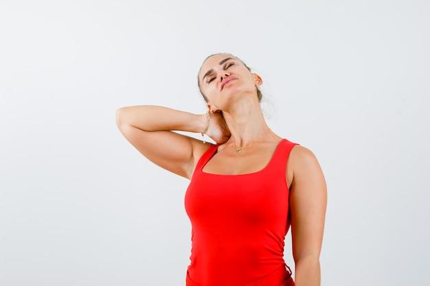 Молодая женщина держит руку на шее в красной майке, штанах и выглядит измученной. передний план.