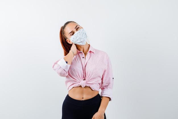 Молодая женщина держит руку на шее в рубашке, штанах, медицинской маске и выглядит измученной. передний план.