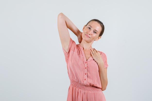 Молодая женщина держит руку на шее в полосатом платье и выглядит расслабленной, вид спереди.