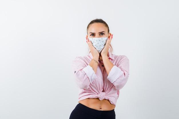 Giovane femmina che tiene le mani sulle guance in camicia, pantaloni, mascherina medica e che sembra fiducioso. vista frontale.