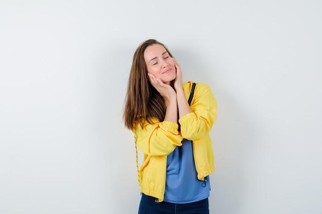 Giovane donna che si tiene per mano sulle guance in maglietta, giacca e sembra pacifica. vista frontale.
