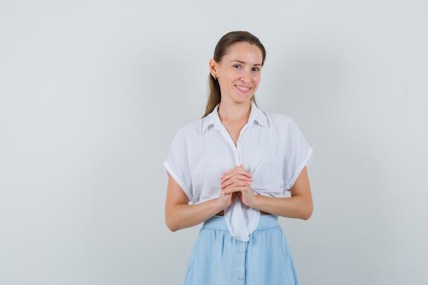 Giovane donna che tiene le mani giunte in camicetta e gonna e sembra fiduciosa