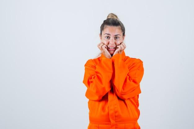Giovane donna che si tiene per mano sulla mascella caduta in uniforme da lavoro e guardando ansioso, vista frontale.