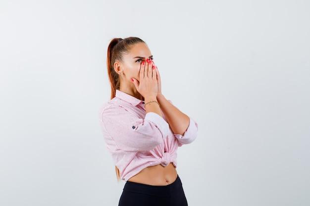 Giovane donna che tiene le mani sul viso mentre cerca in camicia casual, pantaloni e guardando stupito, vista frontale.